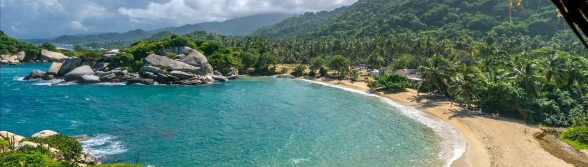 Tayrona National Park holidays - view of gorgeous sandy bay and rainforest backdrop